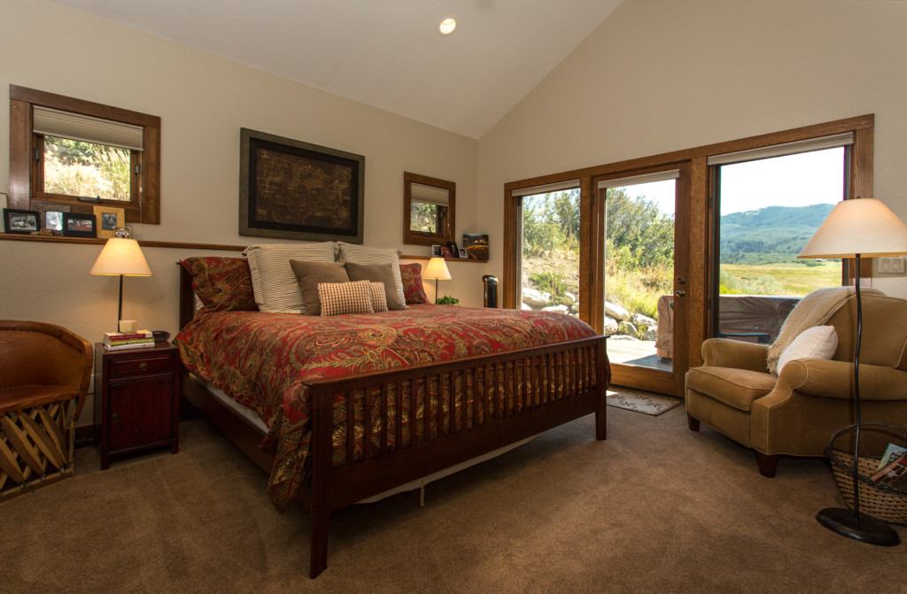 Master suite with hot tub on private deck overlooking open meadow.