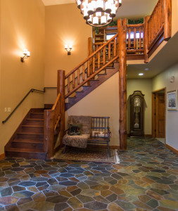 Log accents in the entry, walnut stairs and slate flooring.